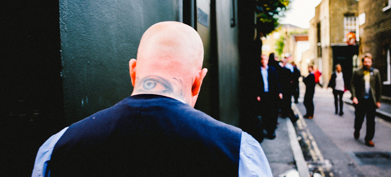 Mann mit Glatze geht einsam die Straße lang